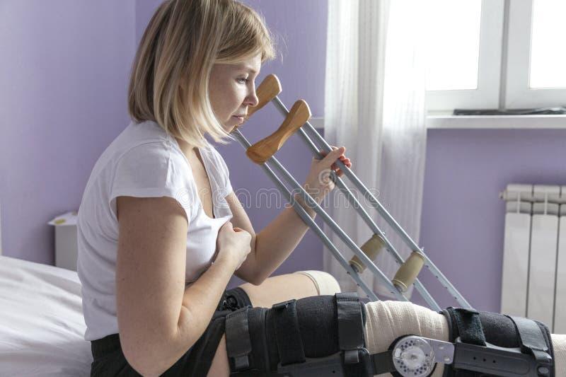 Une jeune femme avec un orthosis sur sa jambe s'assied sur le lit Essaye de se lever avec des béquilles Période postopératoire photographie stock