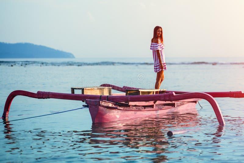 Une jeune femme avec un sourire accompagne la position de coucher du soleil dans un petit bateau rose images libres de droits