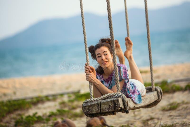 Une jeune femme balançant sur une oscillation en bois à une plage tropicale de bord de la mer photographie stock libre de droits