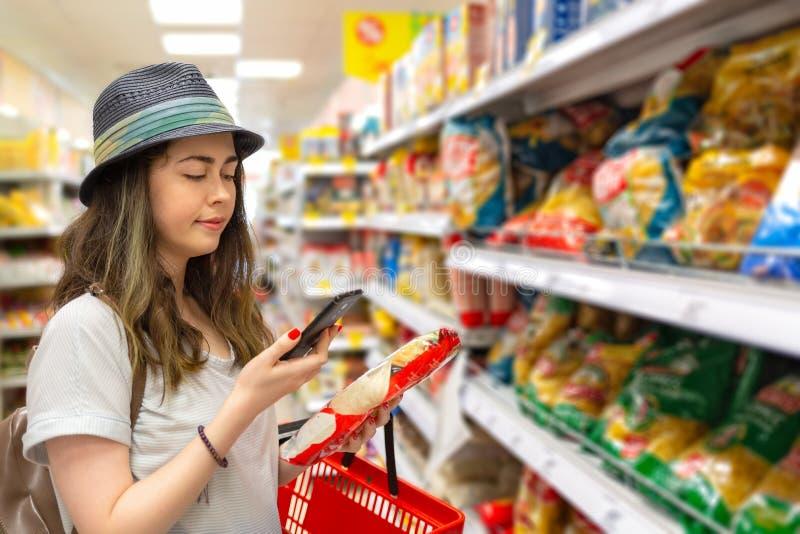 Une jeune femme belle choisit des produits dans le supermarché et vérifie le code QR sur l'étiquette Le concept de technologie mo photographie stock