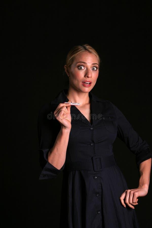Une jeune femme blonde attirante est choquée pour penser qu'elle est enceinte image stock