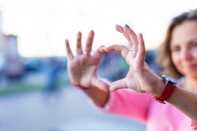 Une jeune femme brune caucasienne élégante regardant à travers un binoculaire imaginaire dans la rue d'été images stock