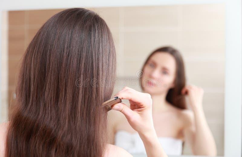 Une jeune femme brune en train de se tresser les cheveux photos libres de droits