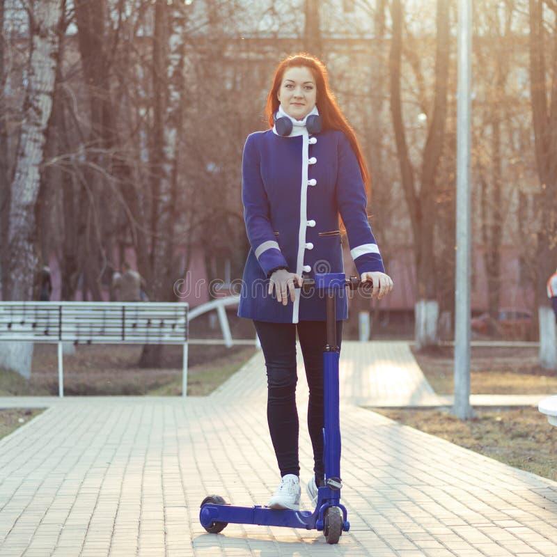 Une jeune femme caucasienne avec les cheveux rouges dans un manteau bleu sur un scooter ?lectrique bleu en parc Transport qui res photo stock