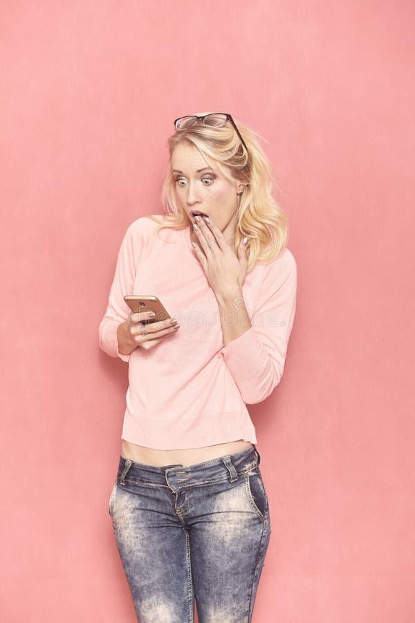 Une jeune femme choqu?e et stup?faite, regardant ? son smartphone photo stock
