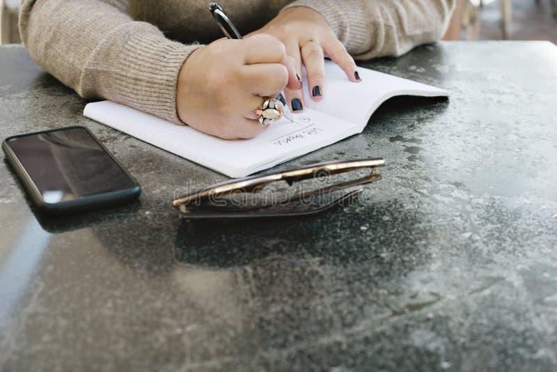 Une jeune femme commence à noter ses buts de la vie dans un journal photographie stock libre de droits