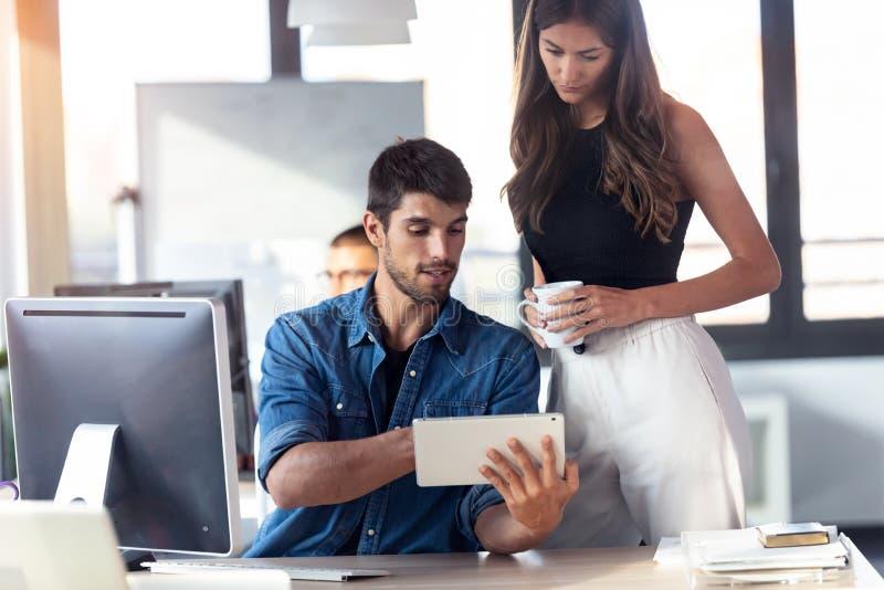 Une jeune femme concentrée debout à côté de son collègue, pointant quelque chose sur une tablette numérique tout en travaillant e photographie stock