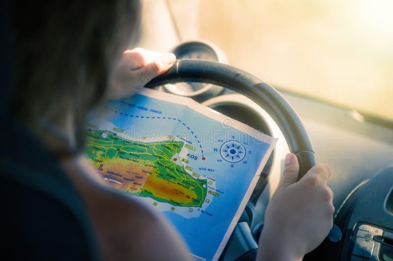 Une jeune femme conduit une voiture et regarde la carte Carte de l'île grecque de Kos La capitale de Kos photo libre de droits