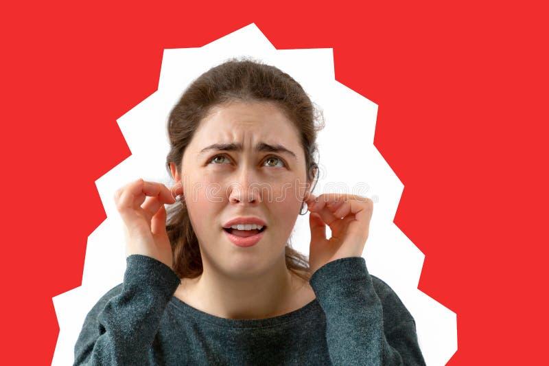 Une jeune femme couvre ses oreilles du bruit ?motion du m?contentement et de l'irritation sur le visage Fond rouge Copiez l'espac images stock