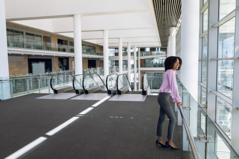 Une jeune femme d'affaires debout dans un lobby d'affaires moderne image stock