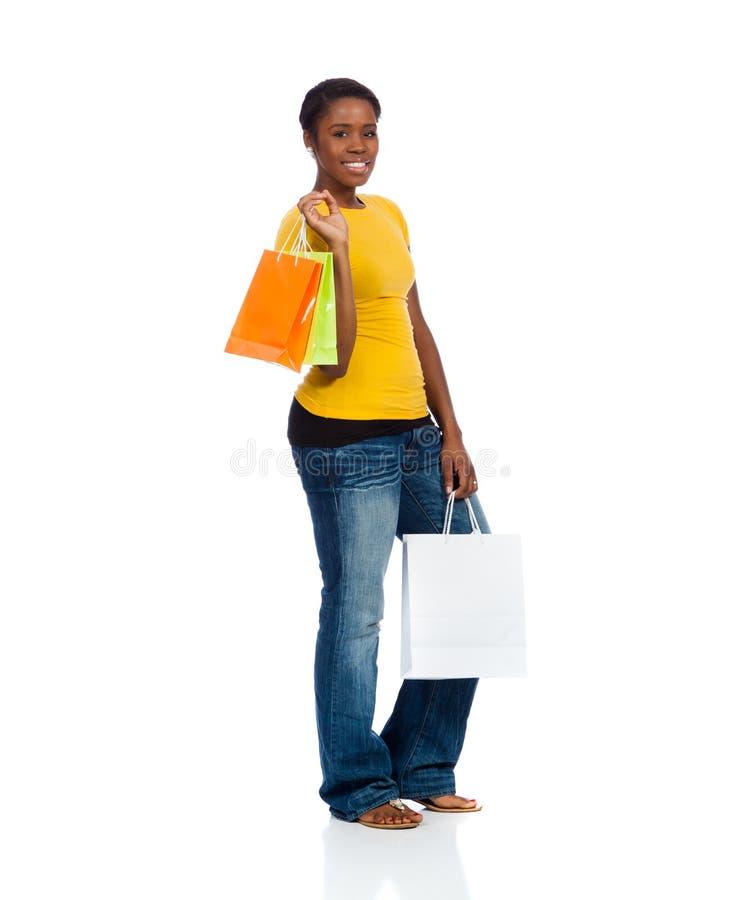 Une jeune femme d'Afro-américain avec des sacs à provisions sur un Ba blanc photographie stock libre de droits