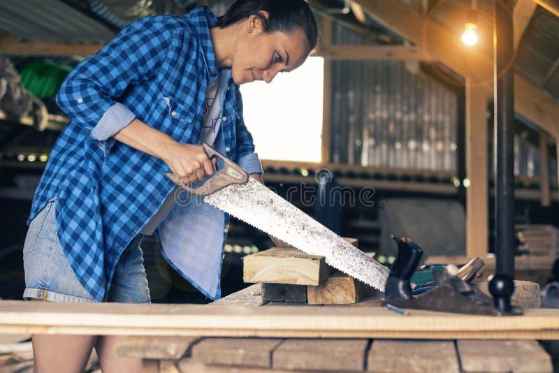 Une jeune femme dans la chambre sciant un conseil, un apprenti du ` s de charpentier photo libre de droits