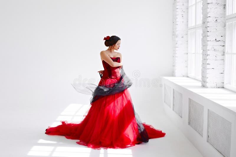 Une jeune femme dans une robe rouge danse Style latin Isolat dessus images libres de droits