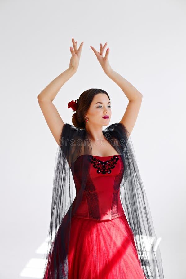 Une jeune femme dans une robe rouge danse Style latin Isolat dessus image stock