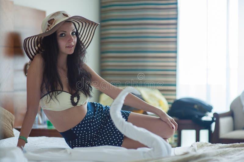Une jeune femme dans un maillot de bain jaune et un chapeau de paille s'assied sur un lit dans une chambre d'hôtel images stock