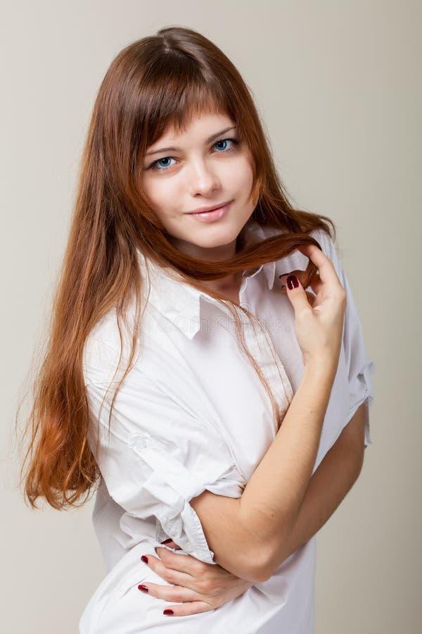 Une jeune femme dans une chemise blanche image stock