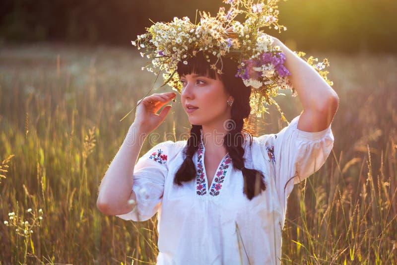 Une jeune femme dans une chemise brodée long par blanc met une guirlande dessus photo stock