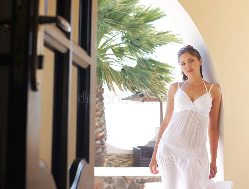 Une jeune femme dans une robe blanche sur un fond de station de vacances image stock