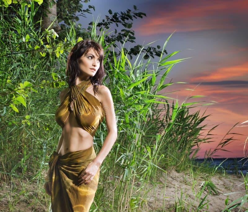 Une jeune femme de brune posant dans la jungle verte images libres de droits