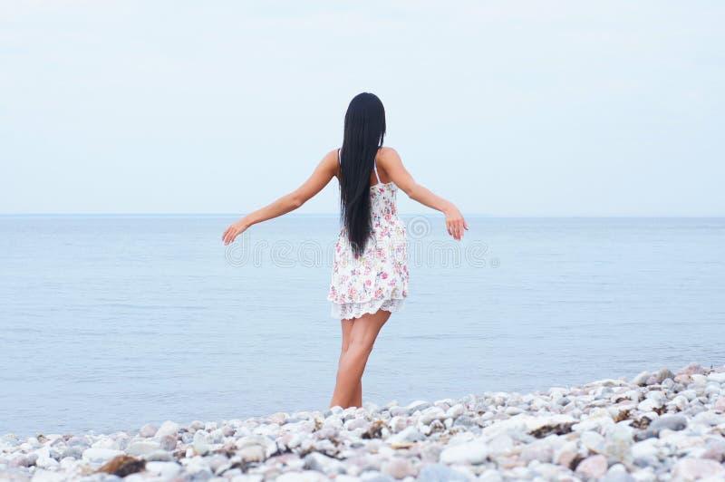 Une jeune femme de brunette posant près de la mer photo libre de droits