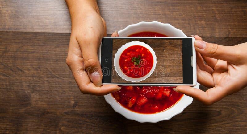 Une jeune femme de mains prenant la photo de la nourriture sur le smartphone photos stock