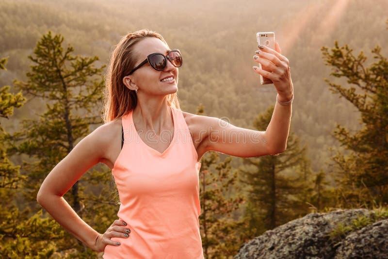 Une jeune femme de sourire fait le selfi sur le smartphone dans les montagnes en été photo libre de droits