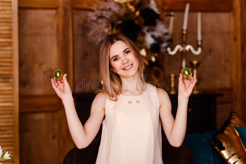 Une jeune femme de sourire tenant deux kiwis Régime de fruit images stock