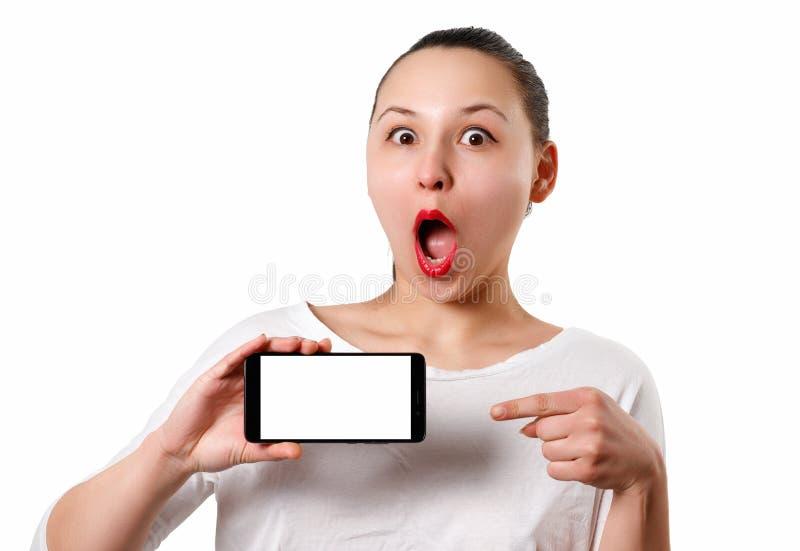 Une jeune femme de sourire tient un smartphone horizontalement avec un ?cran blanc avec un endroit pour le copyspace et des point image libre de droits