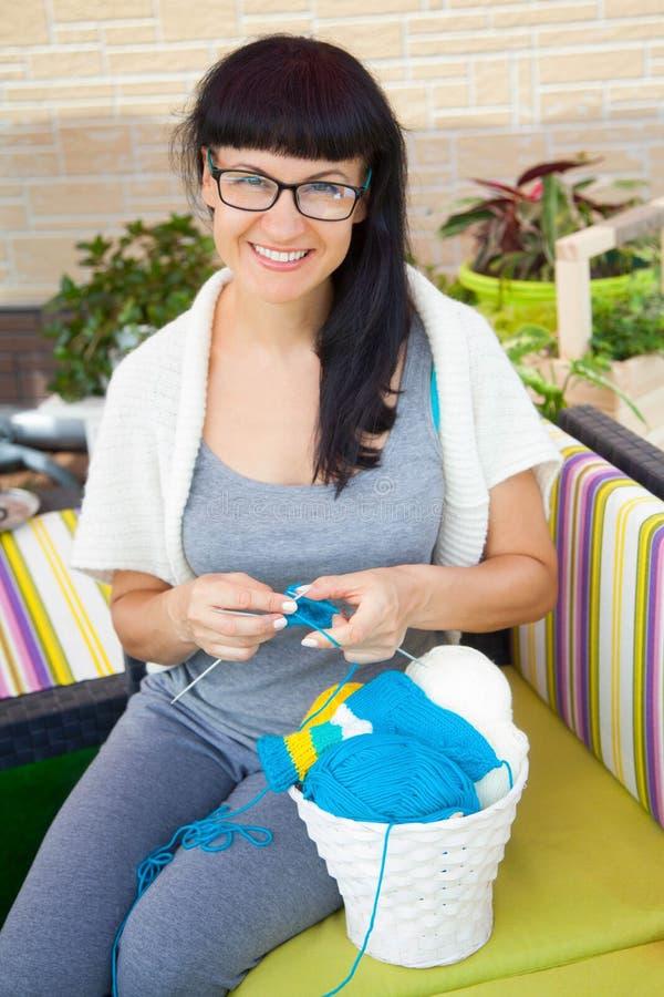Une jeune femme de sourire tricote les chaussettes tricotées avec le woole coloré photographie stock libre de droits