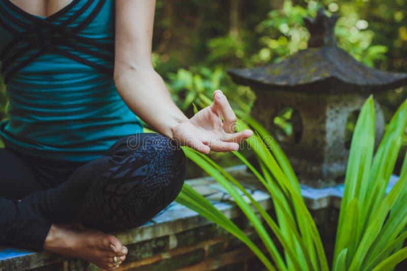 Une jeune femme faisant la méditation dehors dans l'environnement tranquille photos stock