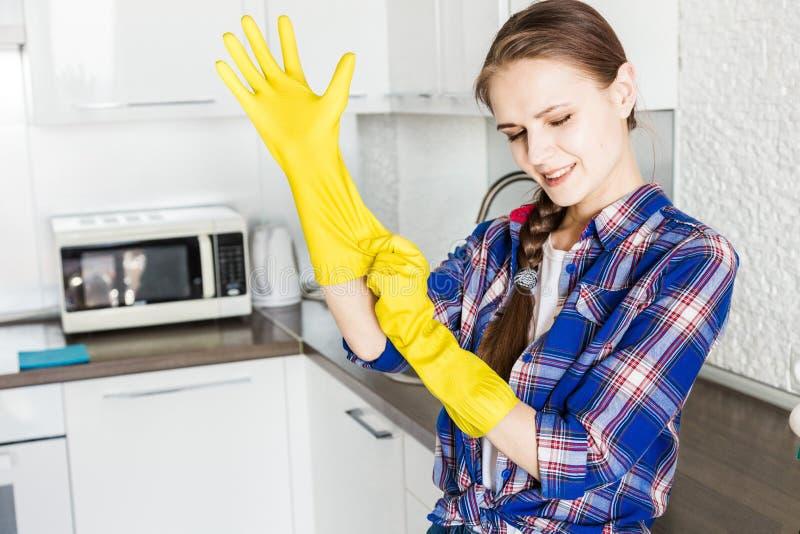 Une jeune femme fait le nettoyage ? la maison, lave la cuisine Seau avec des chiffons et les gants jaunes sur la table image libre de droits