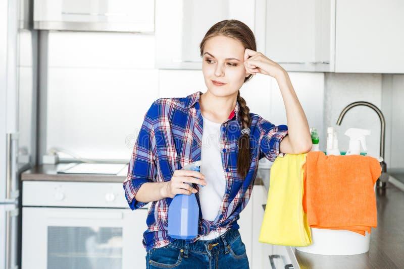 Une jeune femme fait le nettoyage ? la maison, lave la cuisine Seau avec des chiffons et les gants jaunes sur la table photographie stock