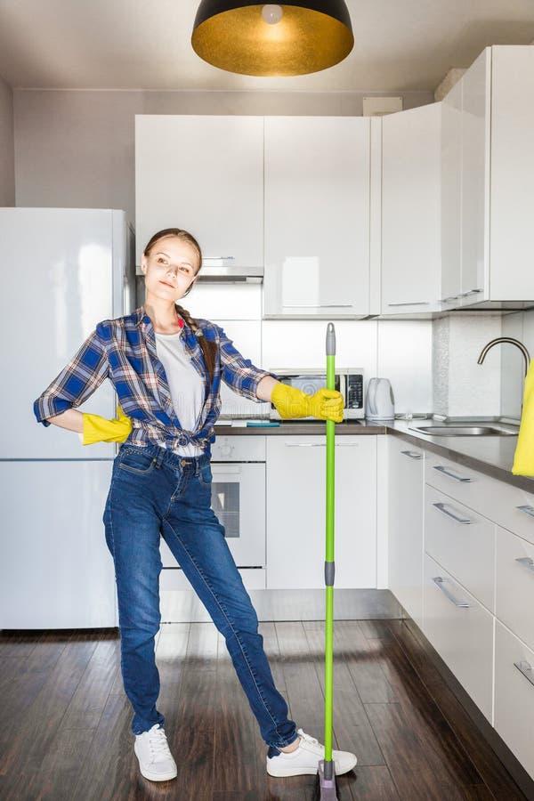 Une jeune femme fait le nettoyage ? la maison, lave la cuisine Seau avec des chiffons et les gants jaunes sur la table photo stock