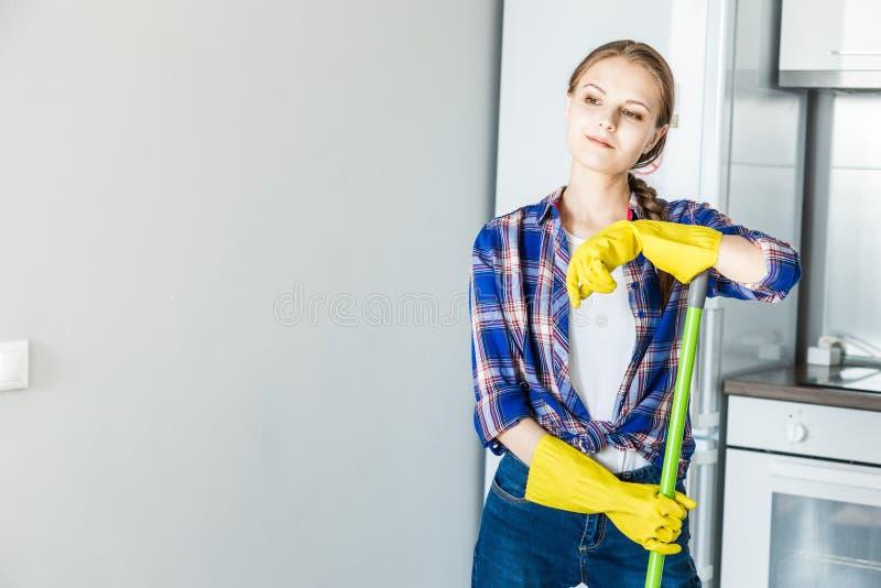 Une jeune femme fait le nettoyage ? la maison, lave la cuisine Seau avec des chiffons et les gants jaunes sur la table photos stock