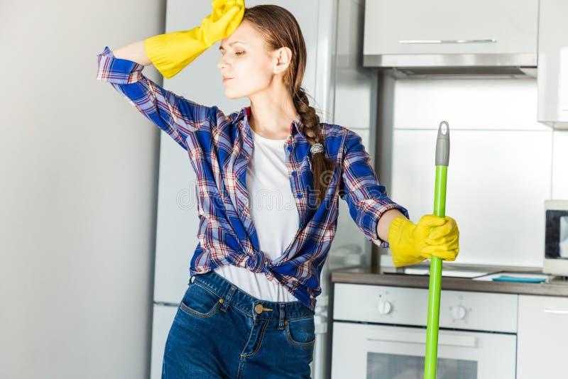 Une jeune femme fait le nettoyage ? la maison, lave la cuisine Seau avec des chiffons et les gants jaunes sur la table photo libre de droits