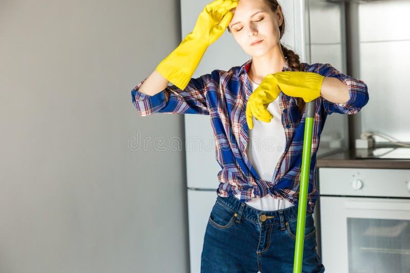 Une jeune femme fait le nettoyage ? la maison, lave la cuisine Seau avec des chiffons et les gants jaunes sur la table photographie stock libre de droits