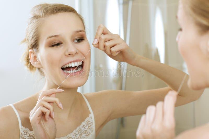 Une jeune femme flossing ses dents image stock