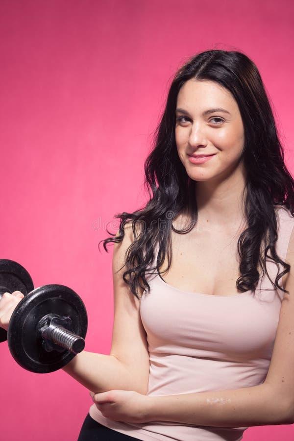 Une jeune femme, haltère pèse se tenant, fond rose images stock
