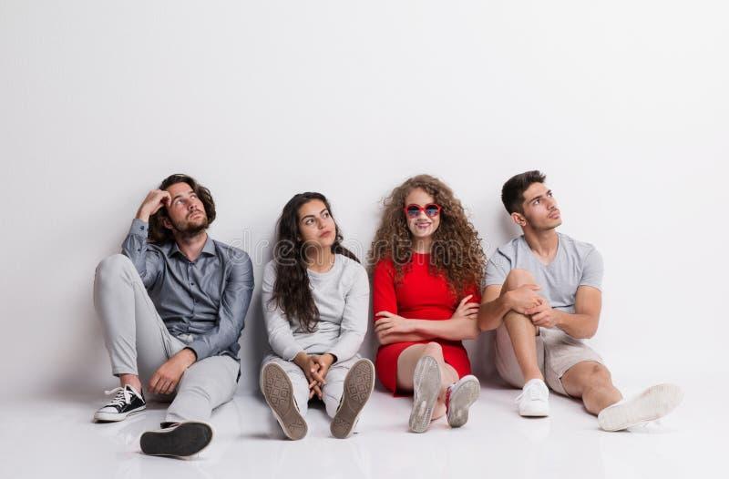 Une jeune femme heureuse avec un groupe d'amis ennuyés s'asseyant sur un plancher photographie stock