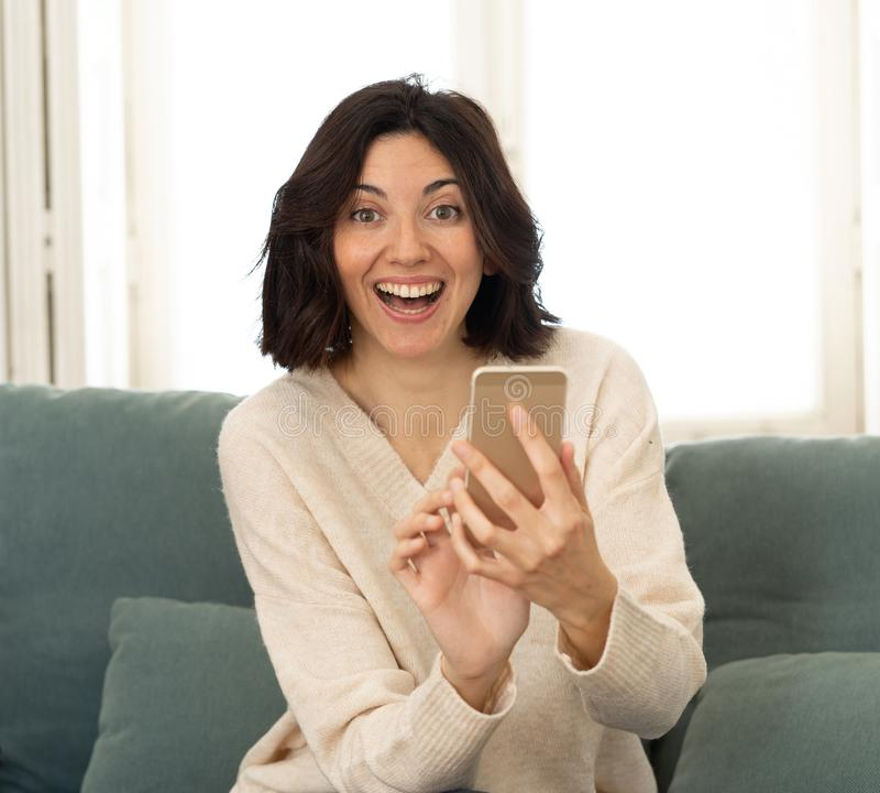Une jeune femme heureuse en utilisant son smartphone assise sur un canapé à la maison Dans les loisirs et l'addiction mobile photos stock