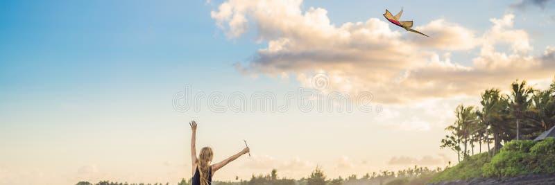 Une jeune femme lance un cerf-volant sur la plage Rêve, aspirations, BANNIÈRE de plans futurs, LONG FORMAT photo stock