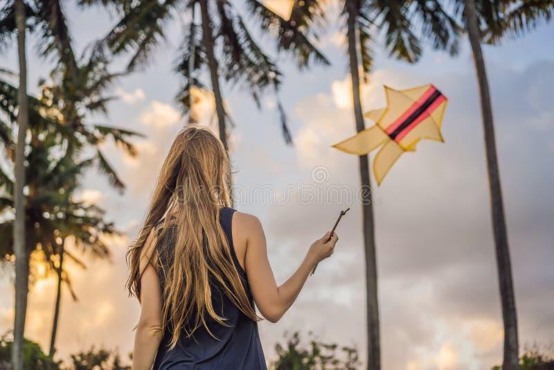 Une jeune femme lance un cerf-volant sur la plage Rêve, aspirations, plans futurs photo stock