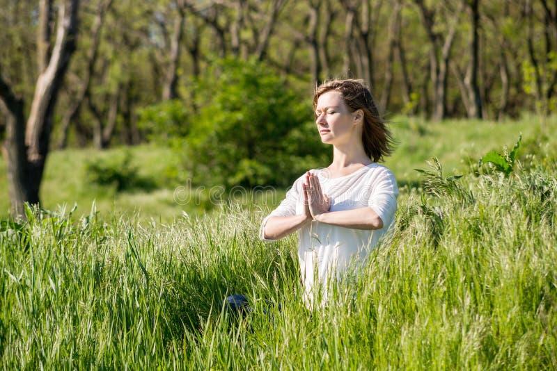 Une jeune femme méditant en parc photo stock