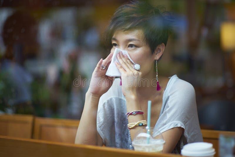 Une jeune femme malade soufflant son nez photos stock
