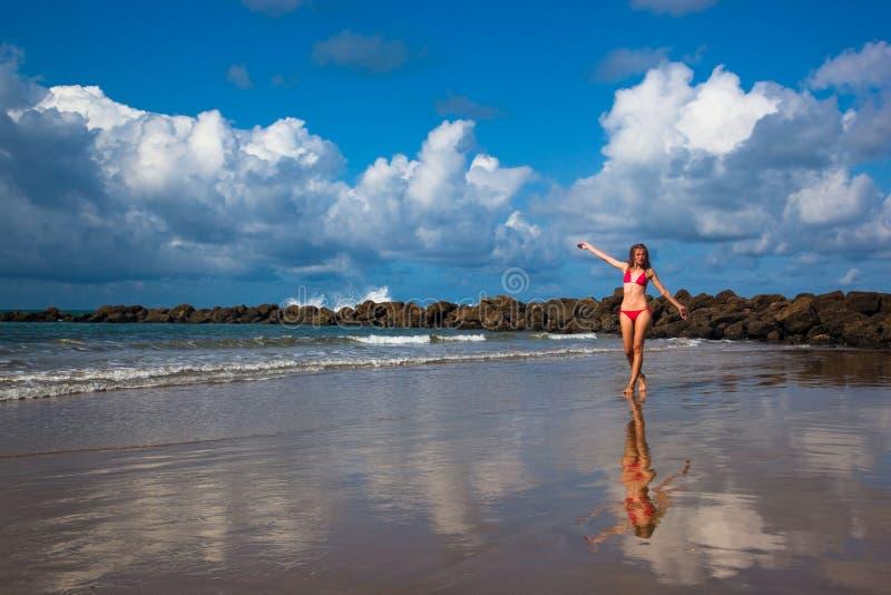 Une jeune femme marchant sur la plage d'océan image stock