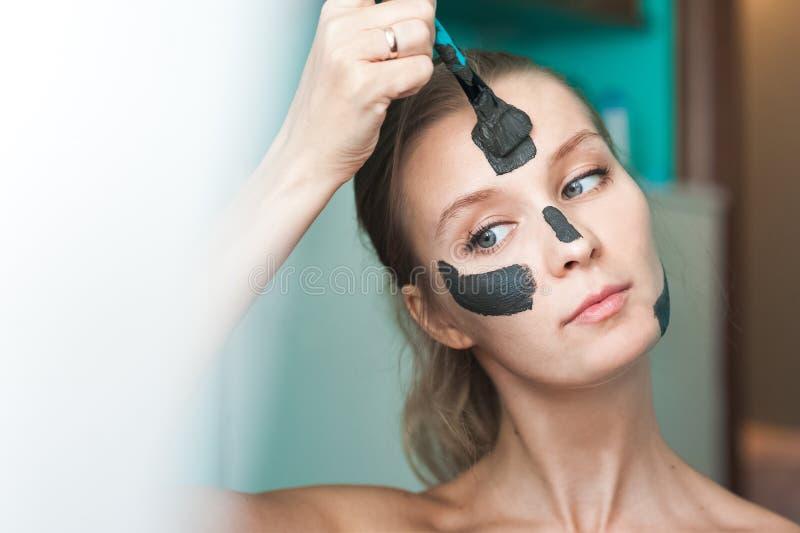 Une jeune femme met un masque noir sur son visage et rit Photo de beauté d'une femme souriant à l'appareil-photo images stock