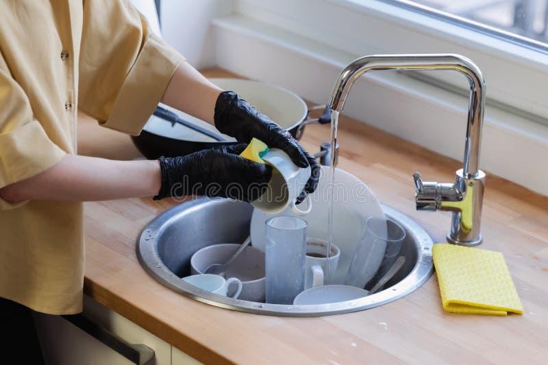 Une jeune femme nettoie dans la cuisine, lavant des plats photo libre de droits