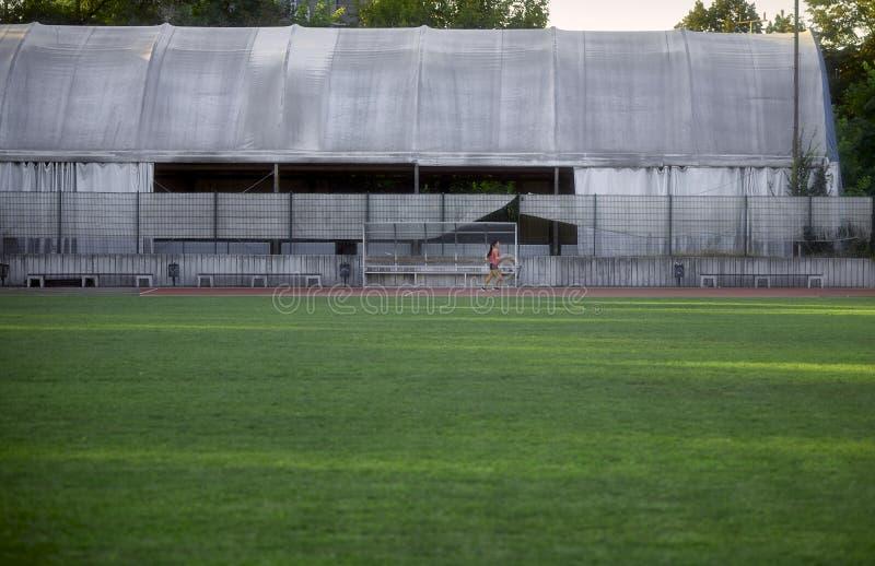 Une jeune femme, petit minuscule dans le tir, seul courant sur les sports et le champ, voies fonctionnantes photo libre de droits