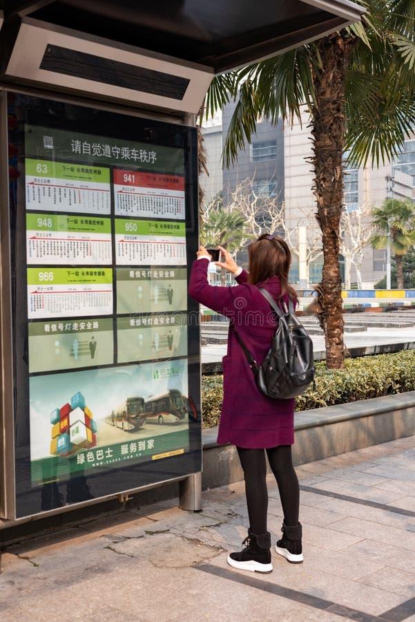 Une jeune femme photographie l'horaire du bus à Zuhai, en Chine image stock