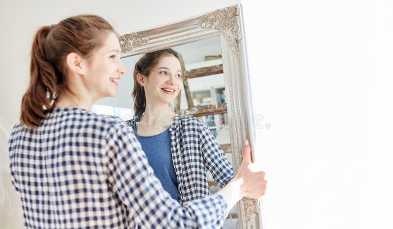 Une jeune femme porte un miroir dans son nouvel appartement photo stock